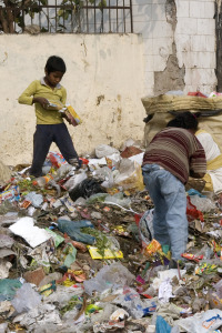 boy stands on garbage pile with food