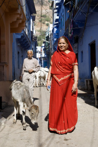 An elderly lady in a red dress in front of blue building fronts